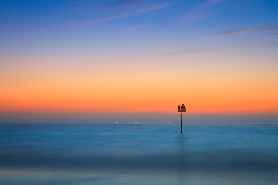 Long exposure photograph of a tide marker in Scheveningen at sunset