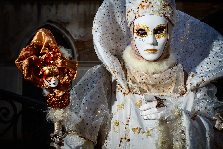 Woman in white Carnival Costume with mask and staff