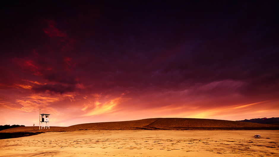 Photograph of a beach at sunrise with a purple sky