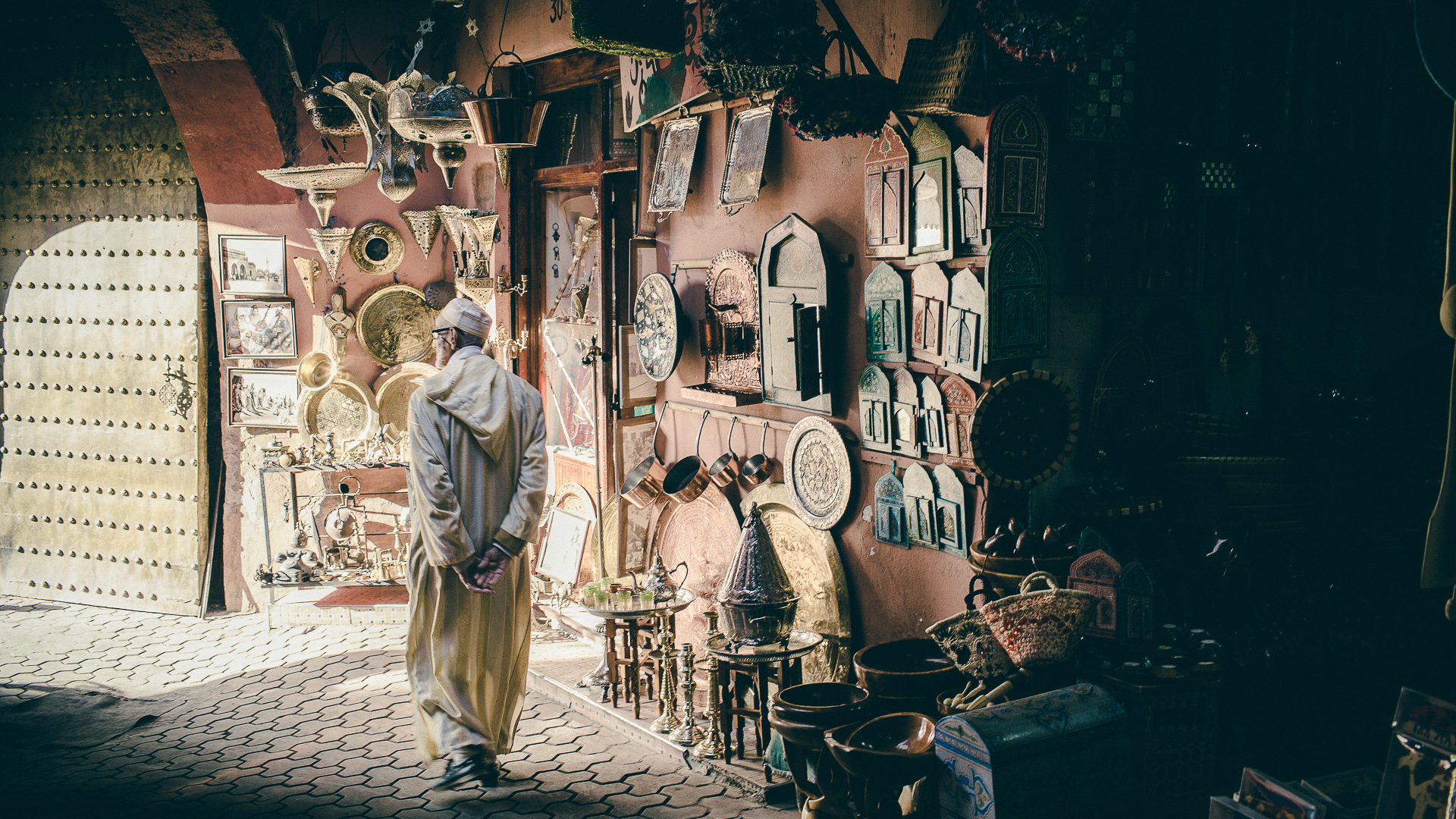 A man walks in a Marrakech souk near sunset